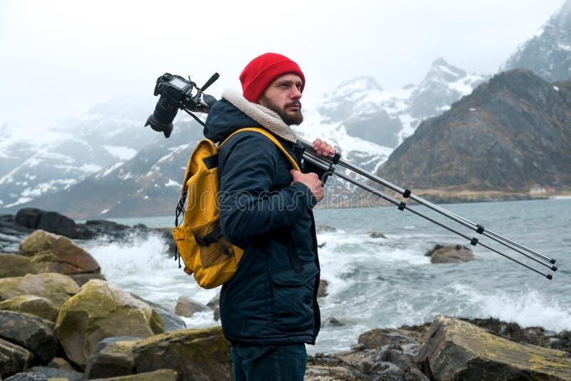 Posição do fotógrafo do homem novo na rocha nas montanhas na praia que fotografa as paisagens em ilhas de Lofoten dentro foto de stock
