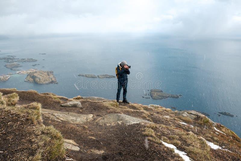 Posição do fotógrafo do homem novo na rocha nas montanhas na praia que fotografa as paisagens em ilhas de Lofoten dentro imagens de stock royalty free
