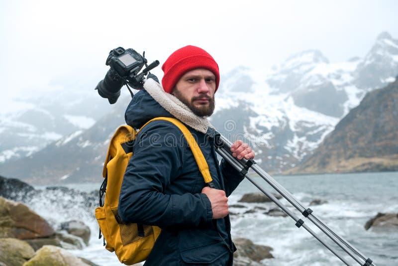Posição do fotógrafo do homem novo na rocha nas montanhas na praia que fotografa as paisagens em ilhas de Lofoten dentro fotografia de stock