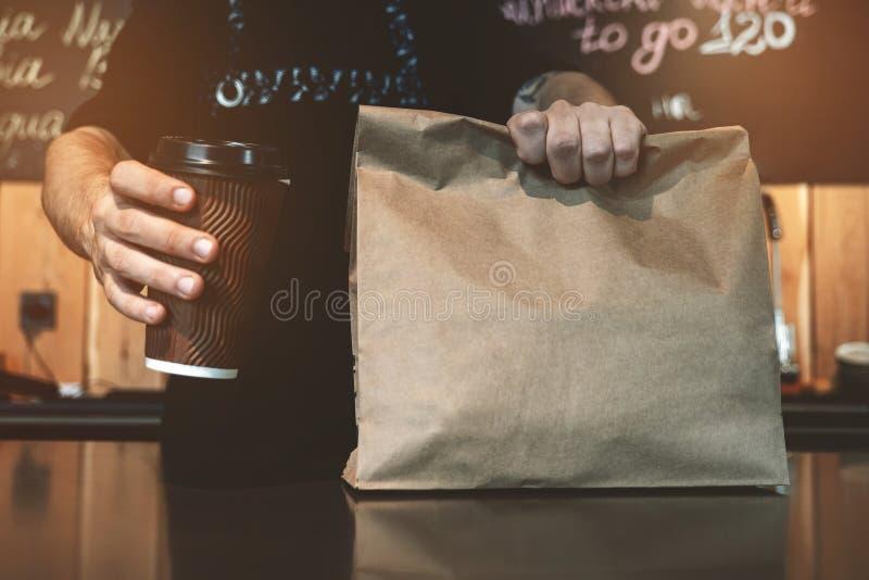 Posição do homem de Barista atrás da barra que guarda a bebida quente do café no saco de papel do copo de papel e do almoço nas m fotos de stock