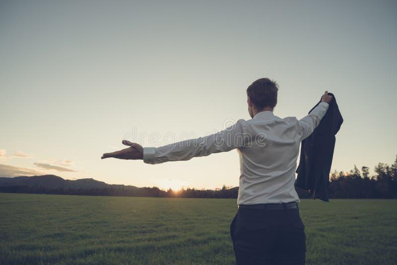 Posição do homem de negócios no prado verde que olha para o por do sol fotos de stock royalty free