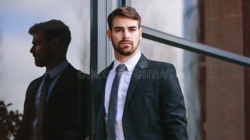 Posição do homem de negócios pelo prédio de escritórios fora fotos de stock royalty free