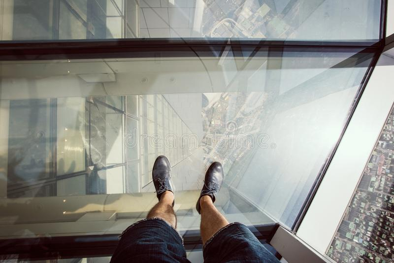 Posição do homem em um assoalho de vidro na plataforma de observação de Lotte Tower imagem de stock
