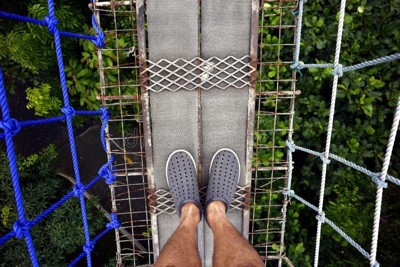 Posição do homem em uma ponte de suspensão imagem de stock royalty free
