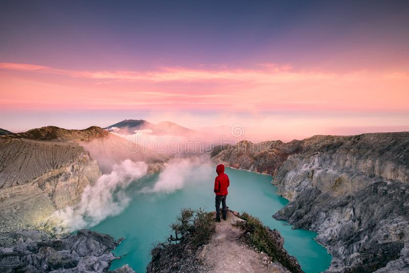 Posição do homem na borda da cratera com o céu colorido na manhã imagens de stock
