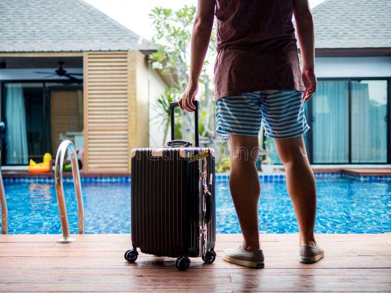 Posição do homem novo com a mala de viagem do curso pela associação Bandeira de viagem do projeto de conceito das férias de verão fotografia de stock