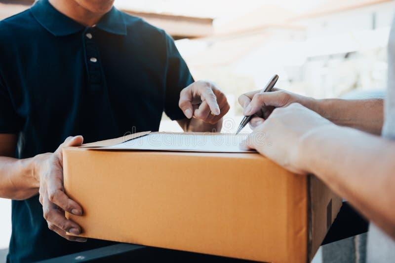Posição do homem novo da entrega na porta da casa e de pacotes levando para o homem novo à assinatura fotos de stock