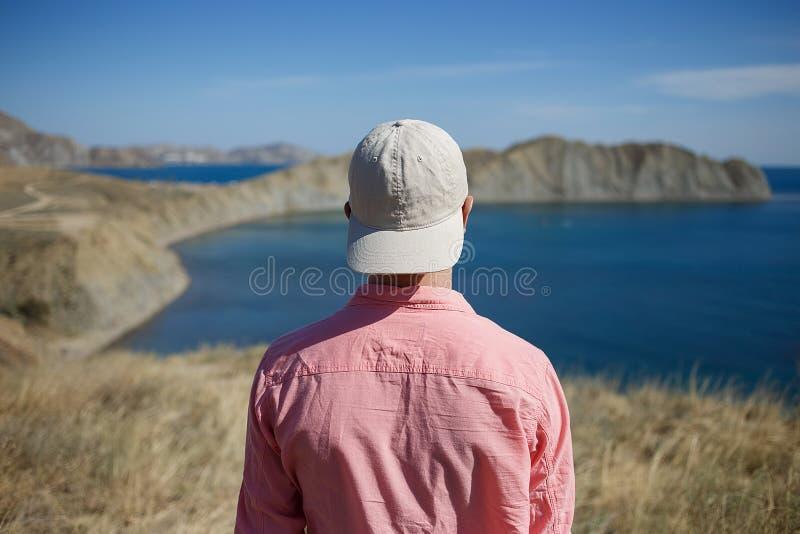 Posição do homem novo em uma costa da montanha que olha ao mar imagem de stock