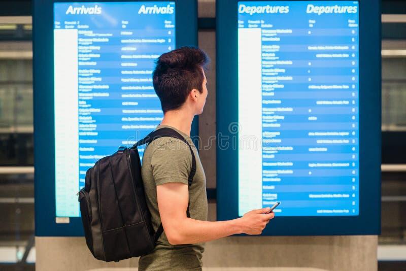 Posição do homem novo na estação de trem ao lado das telas com programação e planejar um curso imagem de stock royalty free