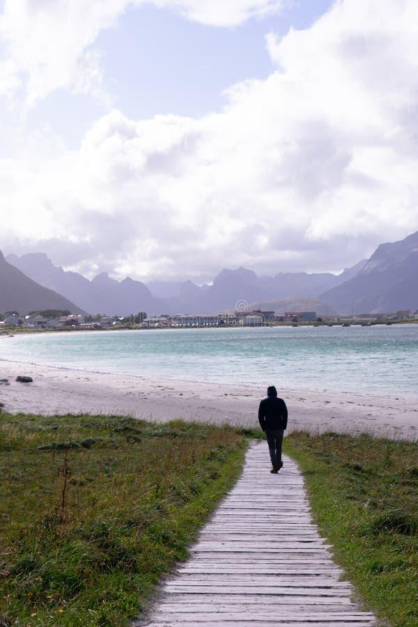 Posição do homem novo na praia com nuvens e o céu azul o mar em ilhas de Ramberg Lofoten, Noruega Europa imagens de stock