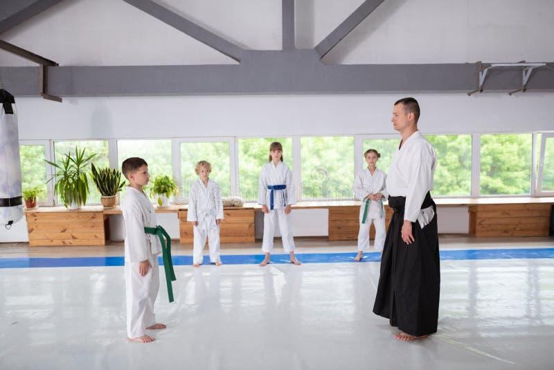 Posição do menino na frente de seu instrutor do aikido antes de praticar fotografia de stock royalty free