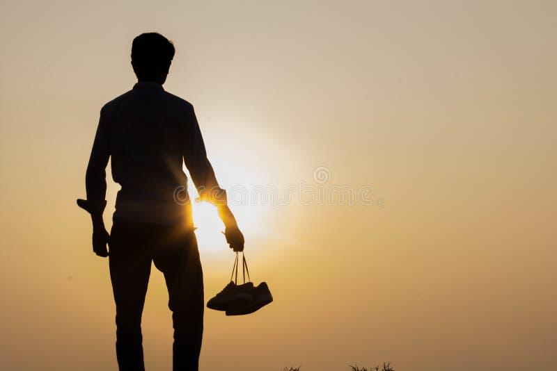 A posição do menino no por do sol e nas sapatas guardar em seu close-up da mão imagem de stock royalty free