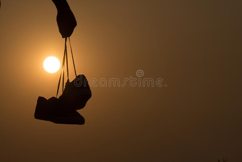 A posição do menino no por do sol e nas sapatas guardar em sua mão Close-up fotos de stock