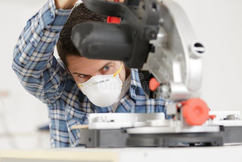 Posição do reparador com a serra elétrica na máscara fotografia de stock