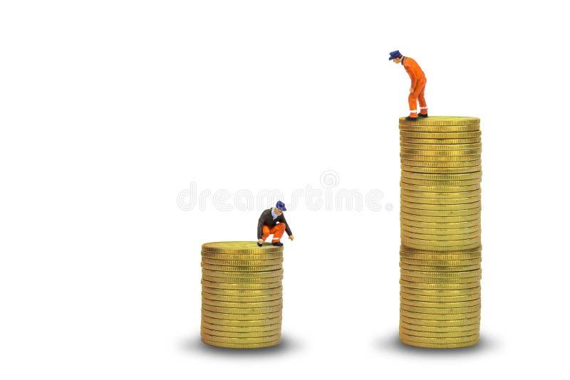 Posição do trabalhador da construção sobre as moedas douradas empilhadas isoladas no fundo branco imagens de stock royalty free