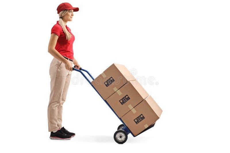 Posição do trabalhador fêmea com caixas em um caminhão de mão fotos de stock royalty free