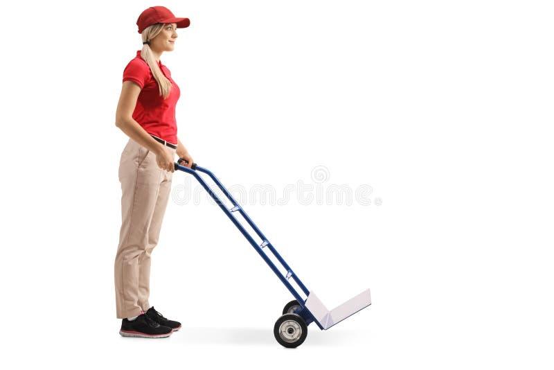 Posição do trabalhador fêmea com um caminhão de mão vazio fotos de stock royalty free