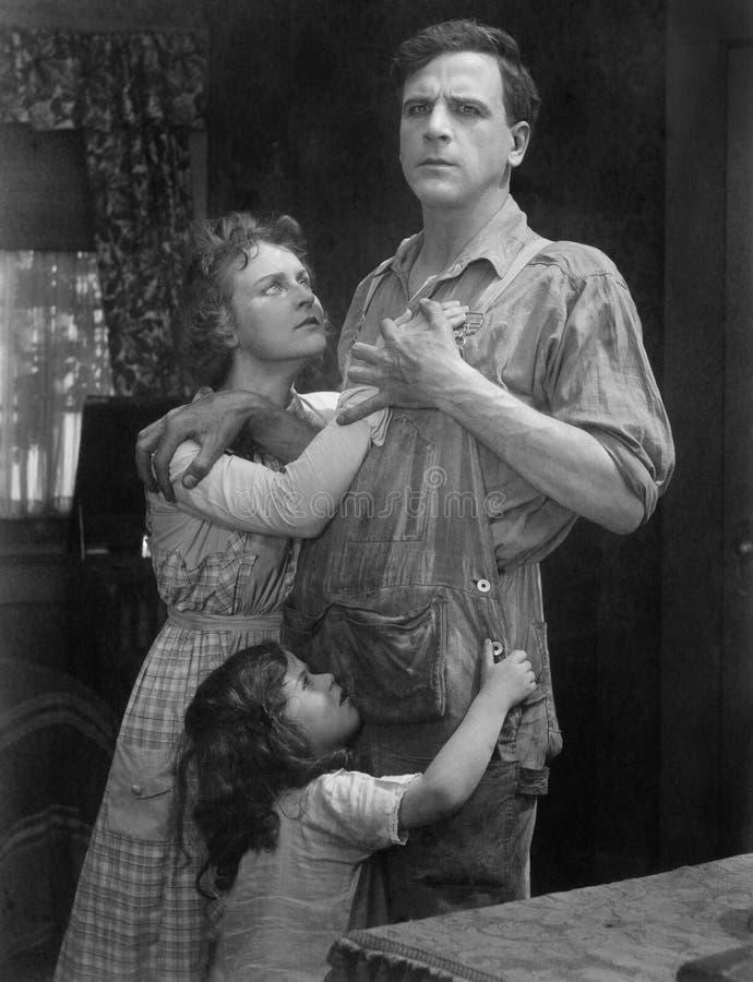 Posição dos pares abraçada com sua filha (todas as pessoas descritas não são umas vivas mais longo e nenhuma propriedade existe W fotos de stock