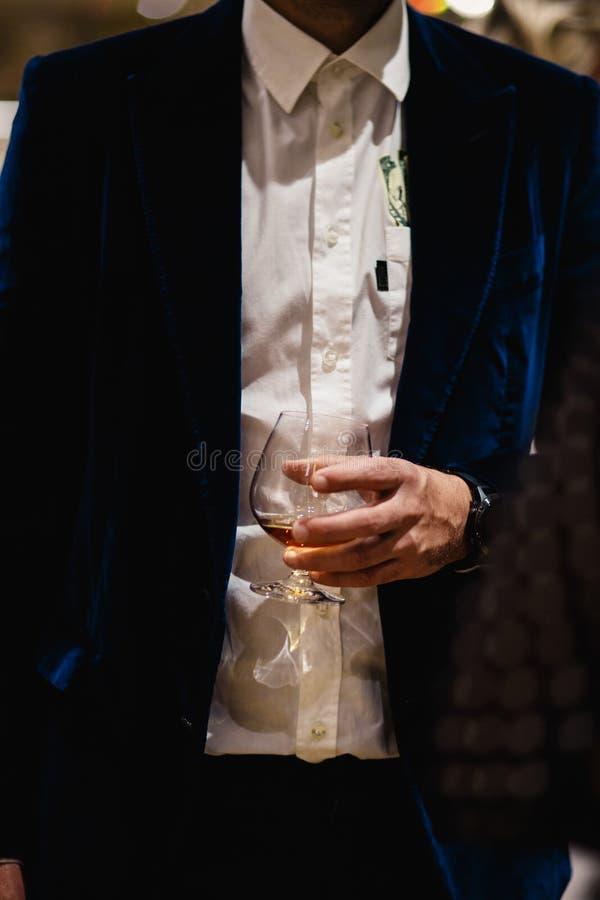 Posição dos povos que conversa em um jantar de negócio que guarda o gosto do vidro do uísque e de vinho e que degustating o alime fotografia de stock royalty free