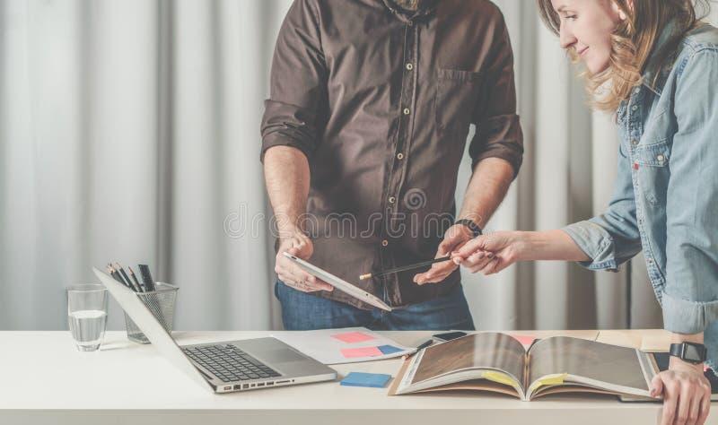 A posição e as mostras da mulher de negócios dos trabalhos de equipa escrevem no tablet pc da tela nas mãos do homem de negócios fotos de stock royalty free