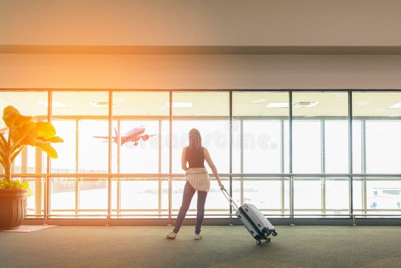 A posição e a mão da mulher do viajante que guardam o saco da bagagem consideram o avião na janela de vidro do aeroporto Turista  imagem de stock
