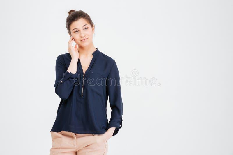 Posição e pensamento bonitos pensativos da jovem mulher fotografia de stock royalty free