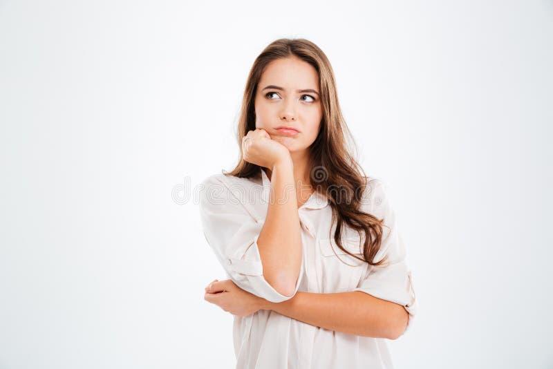 Posição e pensamento bonitos pensativos da jovem mulher foto de stock