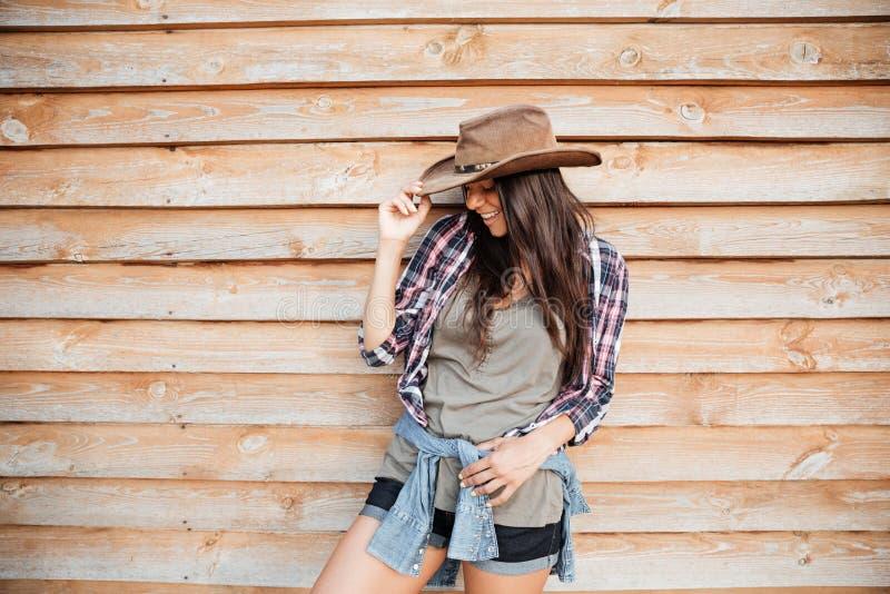 Posição e riso bonitos alegres da vaqueira da jovem mulher imagem de stock