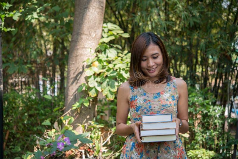 Posição encantador feliz da jovem mulher e cadernos guardar no hom fotografia de stock