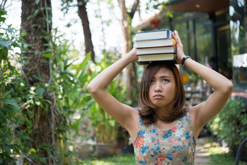 Posição encantador feliz da jovem mulher e cadernos guardar no hom fotografia de stock royalty free
