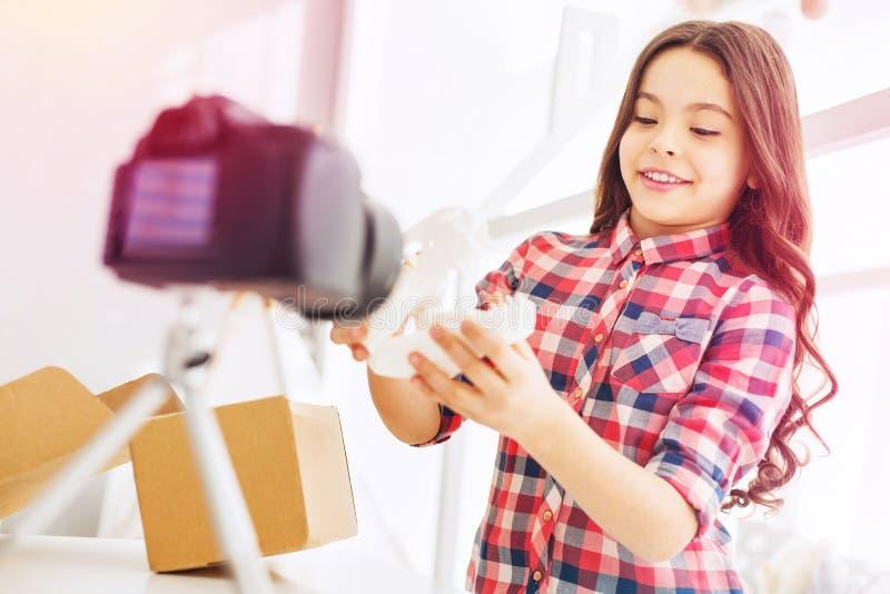 Posição encaracolado à moda e bonita da menina na frente de sua câmera ao filmar o blogue imagens de stock royalty free