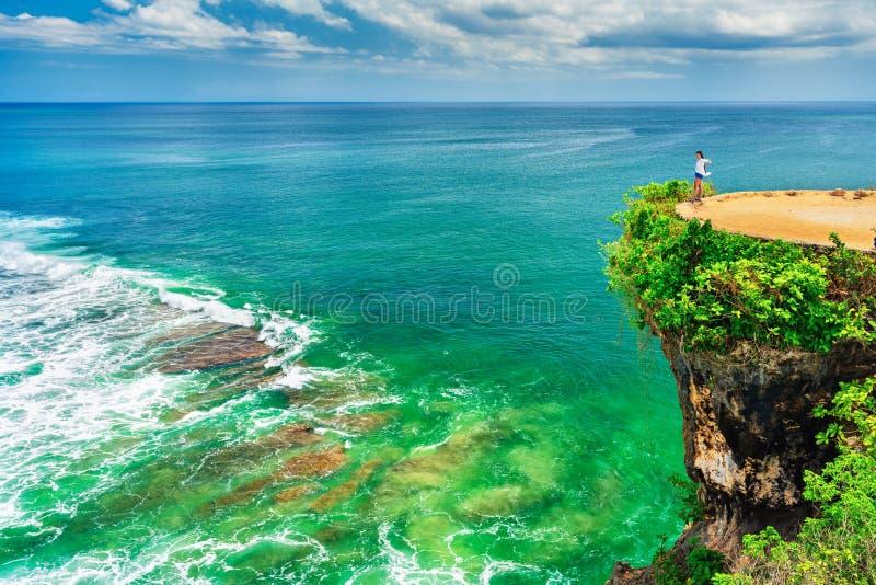 Posição entusiasmado da menina da silhueta no penhasco da montanha e apreciação da praia tropical Balangan da paisagem natural da fotografia de stock royalty free