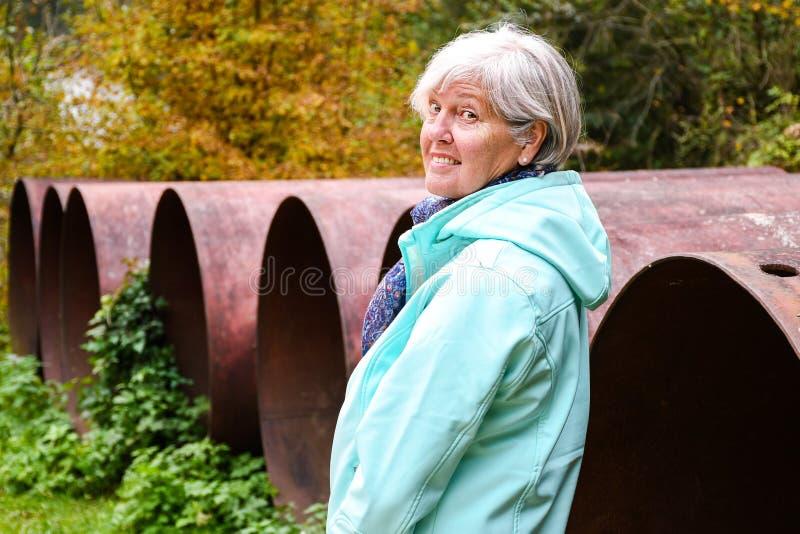 Posição envelhecida média da mulher exterior no outono perto das tubulações velhas grandes da construção da refeição imagens de stock royalty free