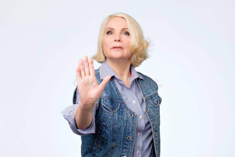 Posição europeia superior da mulher com gesto estendido da parada da exibição da mão fotos de stock