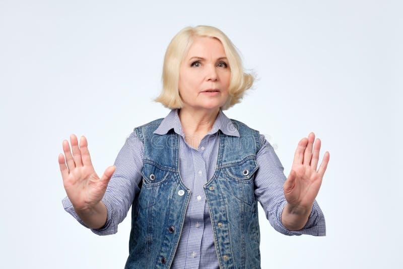 Posição europeia superior da mulher com gesto estendido da parada da exibição da mão fotografia de stock