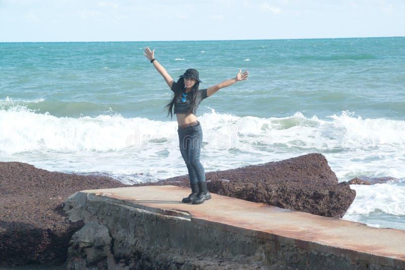 Posição fêmea bonita asiática em rochas com ondas fortes fotografia de stock