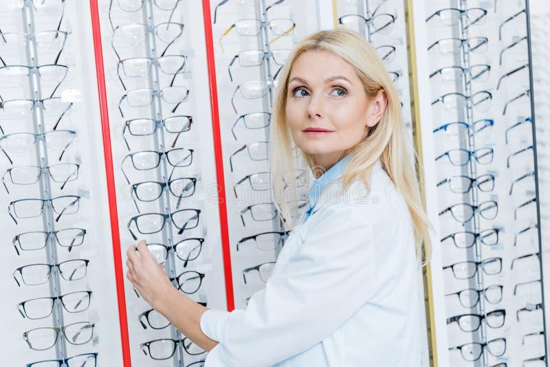 posição fêmea bonita do oftalmologista no sistema ótico com vidros imagem de stock royalty free