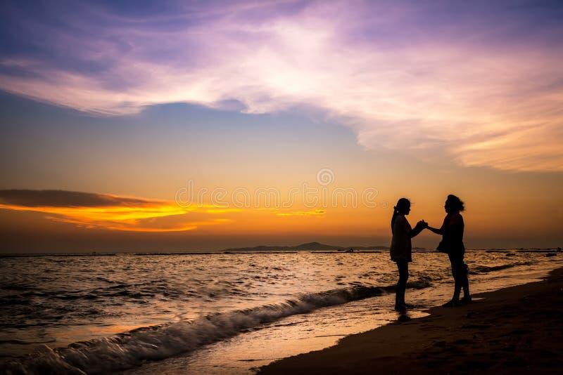 Posição fêmea da silhueta na praia do por do sol imagens de stock