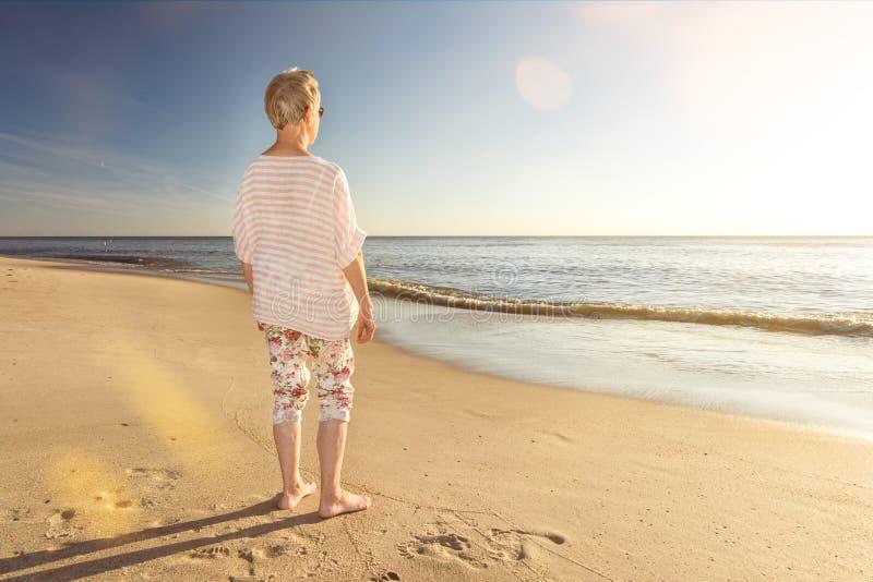 Posição fêmea do aposentado na praia e vista para o oceano com alargamento da lente imagem de stock