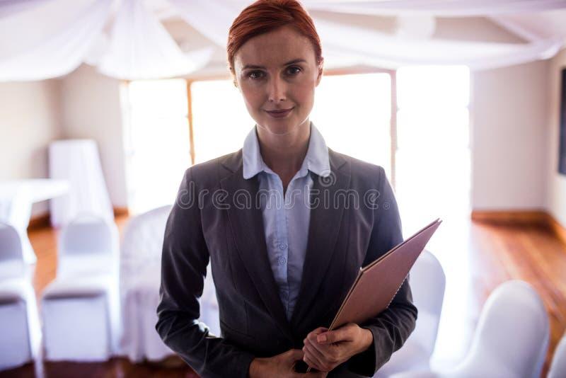 Posição fêmea do gerente com arquivo no hotel imagem de stock