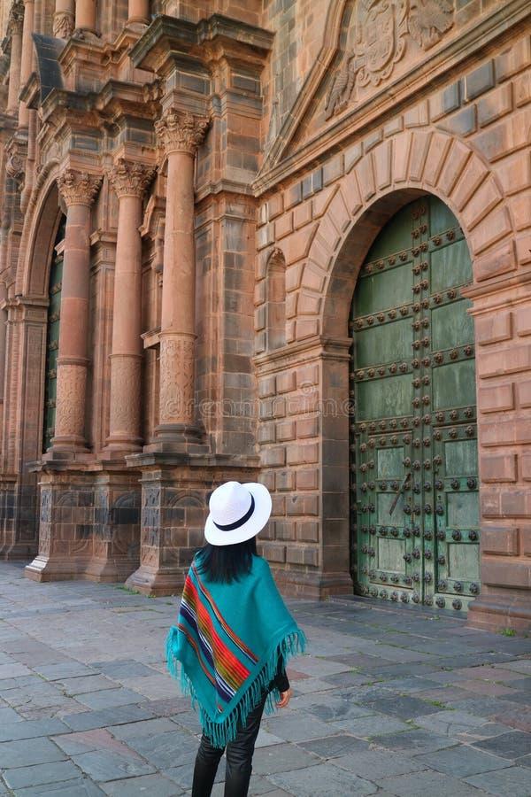 Posição fêmea na frente da porta lindo da catedral de Cusco, Cusco, Peru imagem de stock
