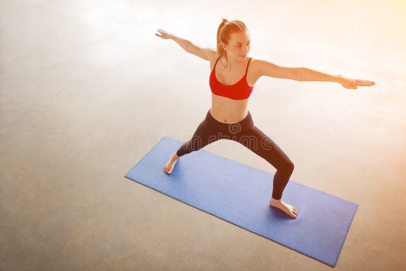 Posição fêmea na pose do guerreiro da ioga imagens de stock