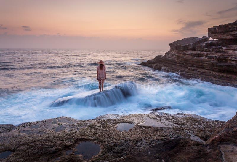 Posição fêmea na rocha do naufrágio com fluxo inundado do oceano sobre ele fotos de stock royalty free