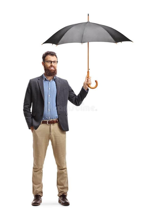 Posição farpada do homem novo e guardar um guarda-chuva aberto fotografia de stock