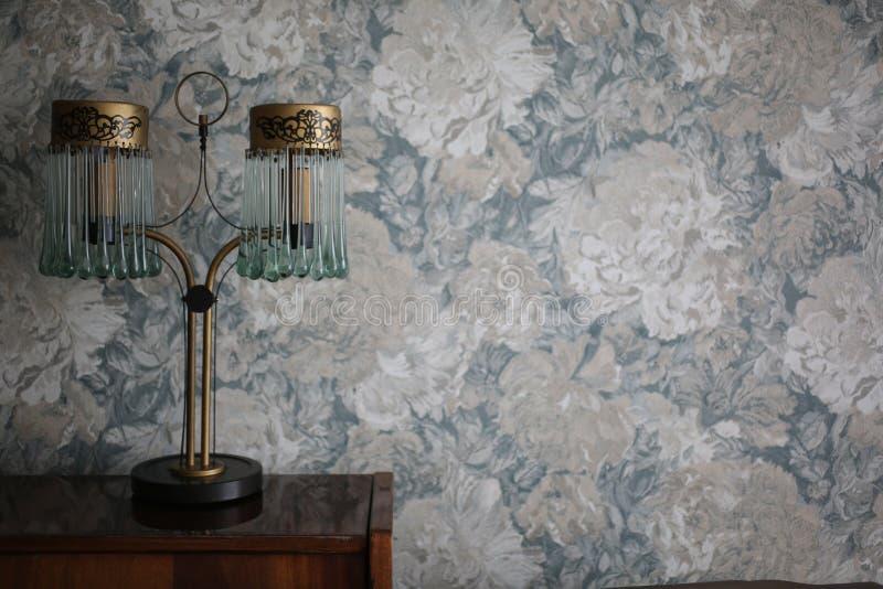 Posição feito a mão da lâmpada do vintage na tabela de madeira Flores pasteis no fundo Lâmpada retro elegante velha para o interi foto de stock