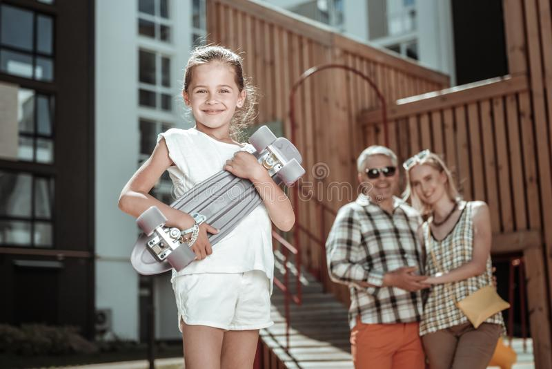 Posição feliz bonito da menina com um skate imagem de stock royalty free