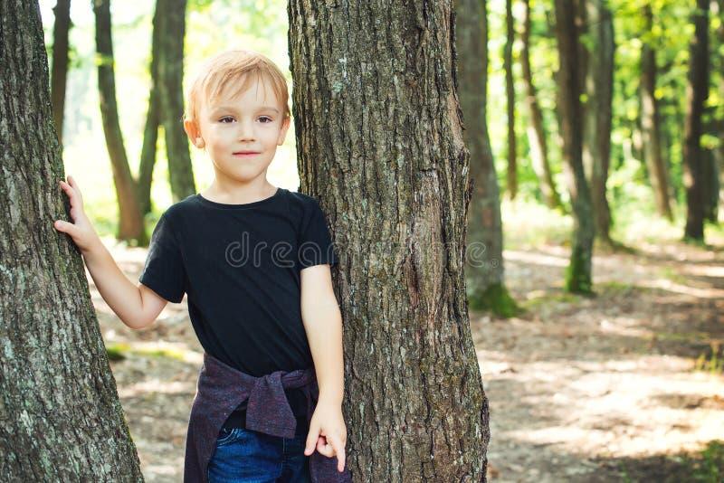 Posição feliz da criança entre árvores em férias em família da floresta no verão Criança feliz que joga no parque Infância feliz  imagem de stock royalty free