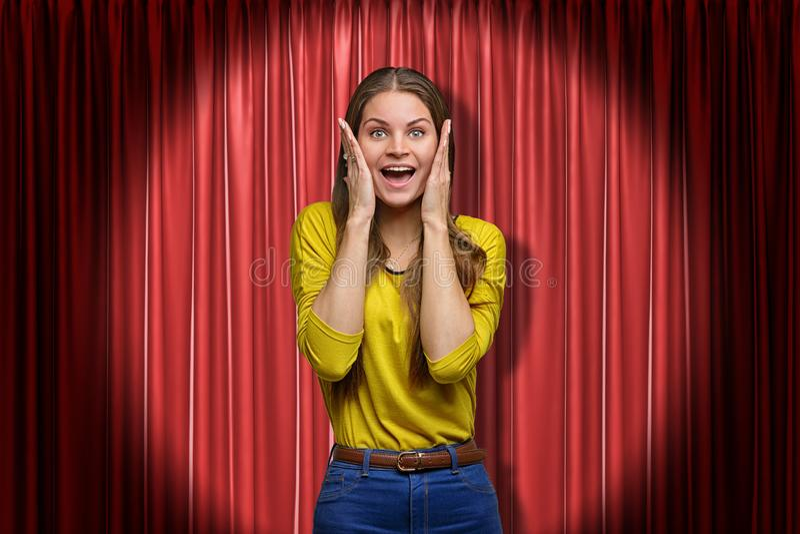Posição feliz da jovem mulher e vista da câmera com mãos na cara, no projetor, contra a cortina vermelha da fase imagens de stock