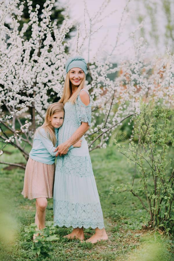 Posição feliz da mamã com filha em um parque da cereja da mola foto de stock