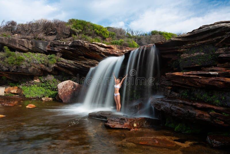 Posição feliz da mulher sob uma cachoeira na região selvagem do bushland foto de stock royalty free